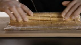 Close-up of chef`s hands rolling a sushi roll on bamboo mat.Sushi making process. Rolls the sushi roll stock footage