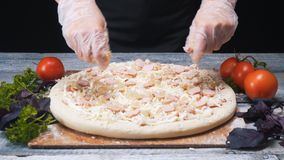 Close-up of chef`s hands in silicone gloves adding cheese to the pizza on a wooden table. Frame. Delicious pizza royalty free stock photos