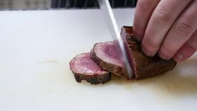 Close-up of chef`s hands, which cuts meat, medium rare steak stock footage