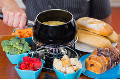 Close up of cheff preparing a gourmet Swiss fondue dinner with assorted cheeses and a heated pot of cheese fondue and. Some vegetable as, broccoli, carrot and Royalty Free Stock Photos