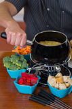 Close up of cheff preparing a gourmet Swiss fondue dinner with assorted cheeses and a heated pot of cheese fondue and. Some vegetable as, broccoli, carrot and Royalty Free Stock Photo