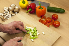 Close up of a chefs hands chopping some salad onions. Close up of a chefs hands cutting some salad onions on a wooden chopping board aside a selection of mixed Royalty Free Stock Image