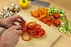 Close up of a chefs hands ring slicing a red bell pepper. Close up shot of a chefs hands ring slicing a cleaned red bell pepper on a wooden chopping board, aside Royalty Free Stock Photos