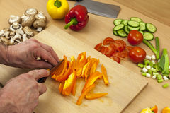Close up of a chefs hands slicing a yellow bell pepper. Close up shot of a chefs hands slicing a cleaned orange bell pepper on a wooden chopping board aside a Royalty Free Stock Photo