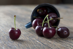 Close-up of cherries in a blue cup on brown background Royalty Free Stock Photography