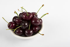 Close-up of cherries in glass bowl on white Royalty Free Stock Images