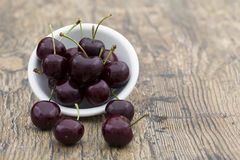 Close-up of cherries in a white bowl on brown background Stock Photo