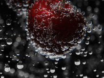 Close up cherry in pure water with bubbles Royalty Free Stock Photography