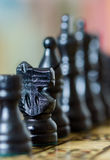 Close up of chess pieces with narrow depth of field. Close up of black chess pieces with focus on the knight, the rest deliberately out of focus with blurred royalty free stock photography