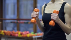 Close up chest of woman shakes biceps with dumbbells in fitness centre stock footage