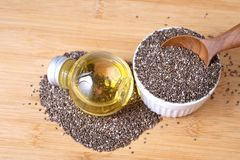 Close up a Chia essential oil and seeds in wooden spoon , superf stock photography