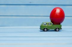 Close up of chicken egg on toy car on a blue wooden background Royalty Free Stock Photos