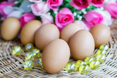Close up chicken eggs and rose in background. Close up chicken eggs lay down on basketwork and rose in background Stock Photo