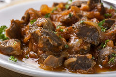 Close up of chicken gizzard stew on plate with herbs Royalty Free Stock Photography