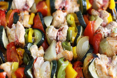Close-up of chicken skewers with bacon and vegetables on a tray. Close-up of chicken skewers with bacon, tomatoes, cucumbers, onions and bell peppers on a tray Stock Photo