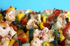 Close-up of chicken skewers with bacon and vegetables on a tray. Stock Photography