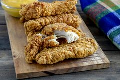 Fried chicken strips with variety of sauces. Close up of chicken strips on wooden cutting board with honey mustard sauce Royalty Free Stock Photos