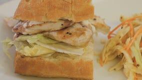 Close-up - chiken o sanduíche com salada de repolho em uma placa branca video estoque