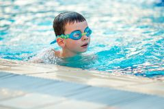 Close up of child boy swimming in pool. royalty free stock photography