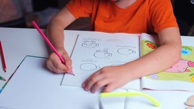 Close-up, child draws with pencil on paper in classroom stock video footage