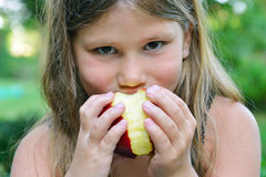 Close up of a Child eating a red apple Stock Photo