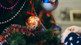 Close-up of child girl hands are decorating a Christmas tree with bright colorful Christmas toys, balls stock footage