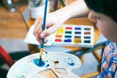 Little boy`s hand holding paint palette and paintbrush mixing the paint. Concept of early childhood education, painting. Close-up child hand painting by royalty free stock photography