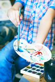 Little boy`s hand holding paint palette and paintbrush mixing the paint. Concept of early childhood education, painting. Close-up child hand painting by stock images