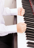 Close up of child hands in fists hitting the piano Royalty Free Stock Images