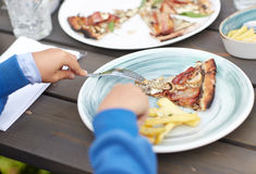 Close up of child hands having dinner outdoors Royalty Free Stock Images