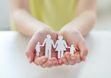 Close up of child hands with paper family cutout. People, charity and care concept - close up of child hands holding paper family cutout at home stock images