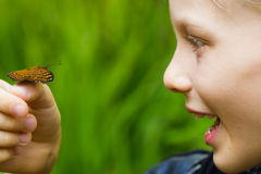 Close-up of child holding a butterfly. Close-up of happy, excited child holding butterfly with green copy-space stock photo