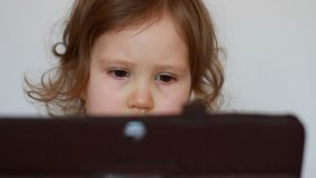 Close-up child looks on the tablet screen and plays downloaded application. A little cute girl is sitting at a table. Looking tv, cartoon and playing the game stock video footage