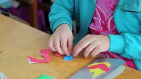 Close-up of a child makes a paper application during a classroom lesson.  stock video