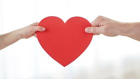 Close up of child and male hands holding red heart Stock Image