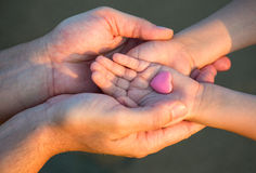 Close up of child and man hands with heart Stock Image