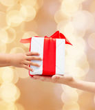 Close up of child and mother hands with gift box Royalty Free Stock Photos