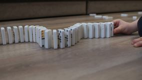 Close-up of a child playing with dominoes at home on the floor.