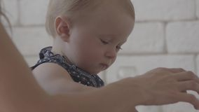Close-up of child playing with the jar of cereals while her mother helping her. Young woman in the kitchen with her baby stock footage