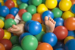 Close-up of a child`s feet in a ball pool Stock Photos