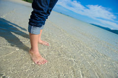 Close up of child`s feet walking on crystal clear tropical sea water. royalty free stock images