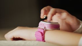 Close-up of a child`s hand with a pink smart watch