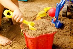 Close up of a child`s hand playing sand toys. stock images