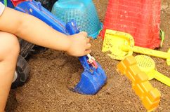 Close up of a child`s hand playing sand toys royalty free stock photo