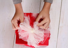 Close up on  child's  hands holding red present with white Ribbon . Gift box packaging. Birthday, New year, Christmas concept. Royalty Free Stock Photos