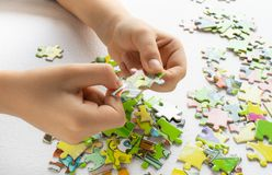 Close up of child`s hands playing with colorful puzzles on light table. Early learning royalty free stock image