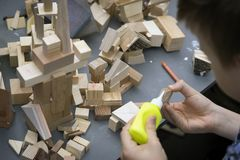 Close-up of child`s hands playing with wooden constructor, bricks on table. Boy glues blocks to make house, building Royalty Free Stock Images