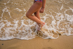 Close-up of child`s legs walking on sand and sea water on beach near Paraty. stock photo