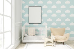 Close up of a child`s room with cloud wallpaper on blue wall. Close up of a child`s room with a vertical framed poster, a cradle, an armchair and a toy horse Stock Photography