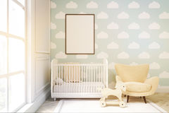 Close up of a child`s room with cloud wallpaper on blue wall. Close up of child`s room with a vertical framed poster, a cradle, an armchair and a toy horse Stock Photography